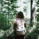 girl with brown hair walking through the woods with a backpack on