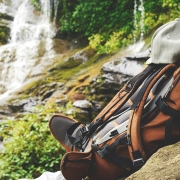 Shallow focus photography of backpack on top of boulder